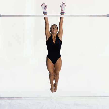 Young gymnast performing on uneven bars, mid-flight