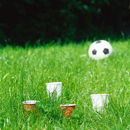 Paper cups in grass, soccer ball in background