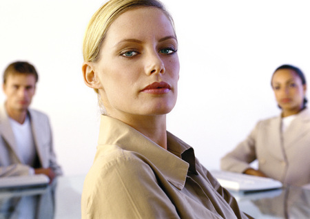 authoritative woman: Woman looking into camera, colleagues in background, portrait
