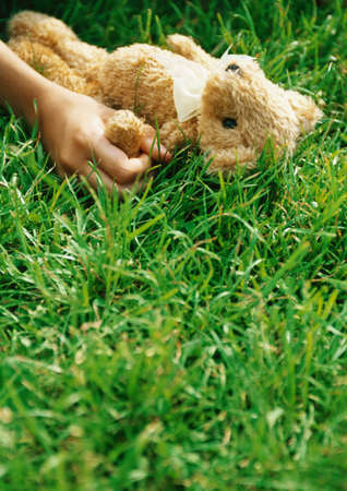 Hand holding teddy bear in grass