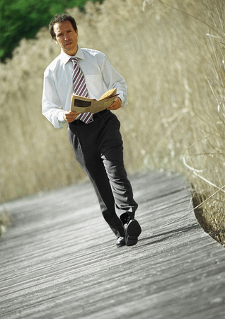 Businessman walking with newspaper in hands, outdoors, portrait LANG_EVOIMAGES