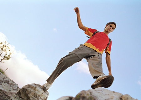 Young man stepping across rocks, low angle view LANG_EVOIMAGES