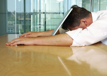 burned out: Businessman lying with face on laptop LANG_EVOIMAGES