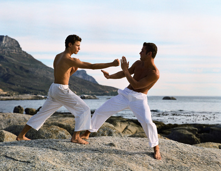 Two men performing martial arts in front of sea