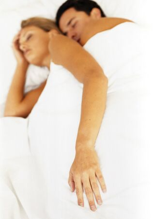 Couple sleeping in bed, focus on womans hand in foreground LANG_EVOIMAGES
