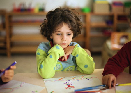 Child sitting at table, head and shoulders