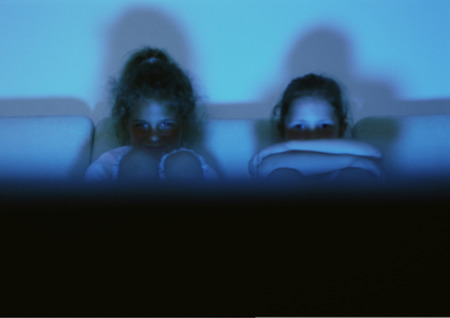 Children sitting on sofa, hugging knees, watching television partial view