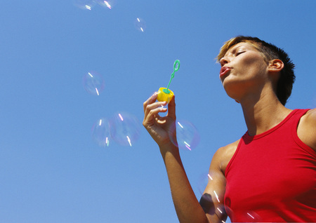 Woman blowing bubbles, low angle view