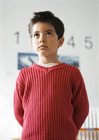 embarrassment: Child holding hands behind back, waist up, close-up