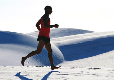 Barefooted man, running across dune, side view LANG_EVOIMAGES