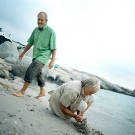 Mature couple on beach, woman digging LANG_EVOIMAGES