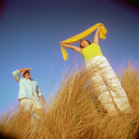 Mature couple standing in tall grass, woman holding scarf above head LANG_EVOIMAGES