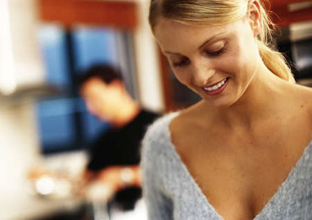 In kitchen, woman smiling and looking down, man in background LANG_EVOIMAGES