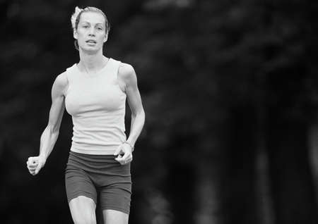 overcoming adversity: Woman in sports clothes running, three quarter length, b&w