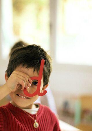 Child looking through plastic letter, portrait