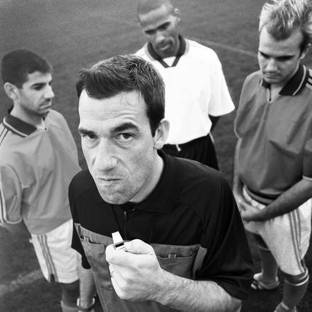 Referee holding whistle in front of three players, looking into camera, b&w