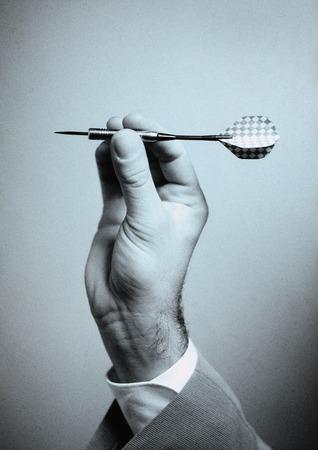 Hand holding dart, close-up LANG_EVOIMAGES