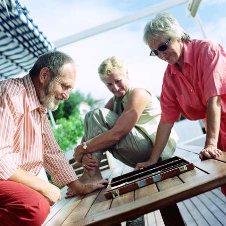 Three mature adults playing backgammon