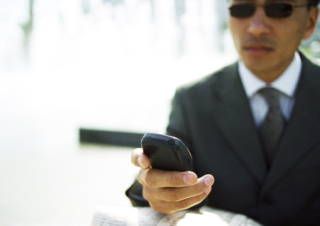 Businessman looking at cell phone, outdoors, close-up LANG_EVOIMAGES