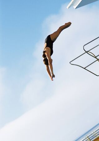 overcoming adversity: Woman in mid-dive, low angle view, full length, blue sky in background LANG_EVOIMAGES