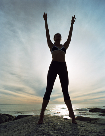 Young woman standing tiptoe, arms up, full length, on rocky shore, sky and seascape in background