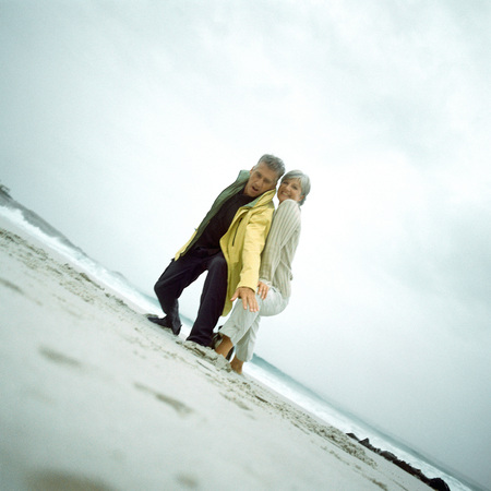 Mature couple on beach looking down into camera