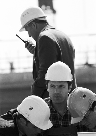 supervisión: Four men with hard hats, one holding walkie-talkie, b&w LANG_EVOIMAGES