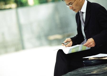 analyses: Businessman sitting outdoors, examining documents