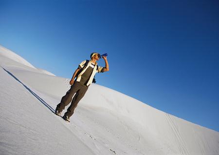 overcoming adversity: Hiker standing on dune, drinking LANG_EVOIMAGES
