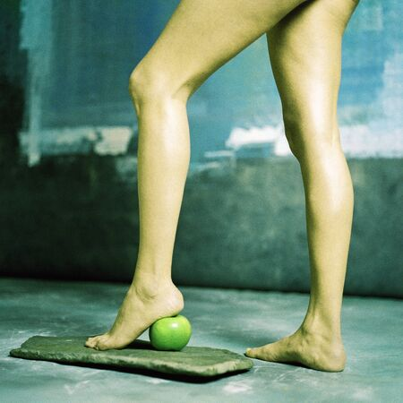 Womans legs, heel on apple, low section LANG_EVOIMAGES