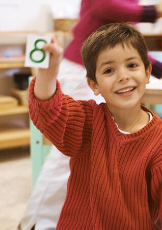 Child holding card, smiling