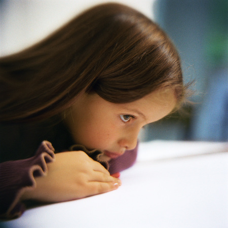 distractions: Girl leaning on table, side view