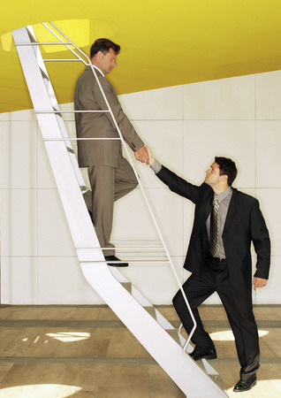 Two men standing on ladder, shaking hands