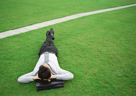 joblessness: Man lying on grass, head on briefcase