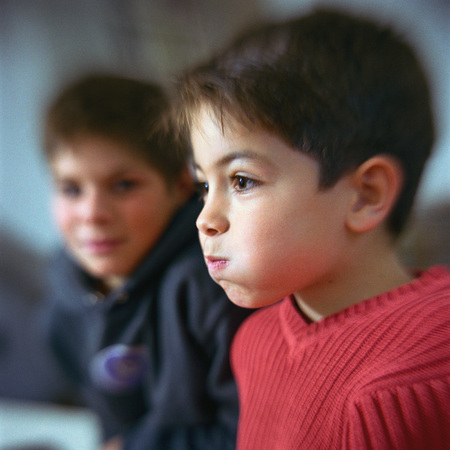 Boy puffing cheeks out, second boy looking at him in background