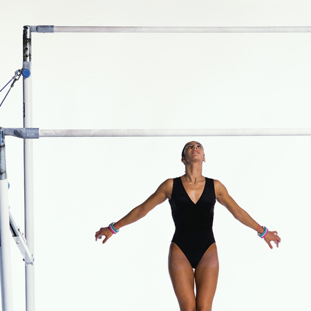 Young female gymnast under uneven bars