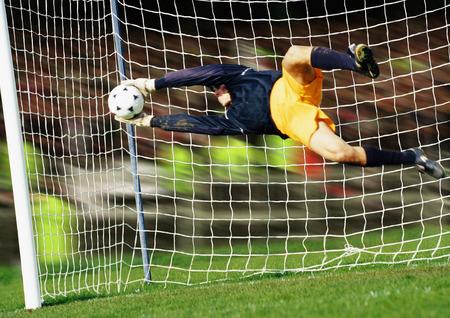 overcoming adversity: Goal keeper, horizontal, saving ball during match, full length LANG_EVOIMAGES