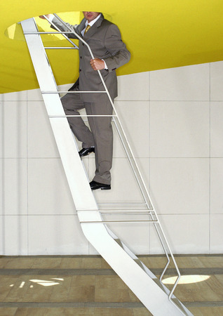 Man in suit, standing on stairs LANG_EVOIMAGES