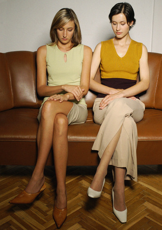 Two women sitting on sofa, looking down LANG_EVOIMAGES