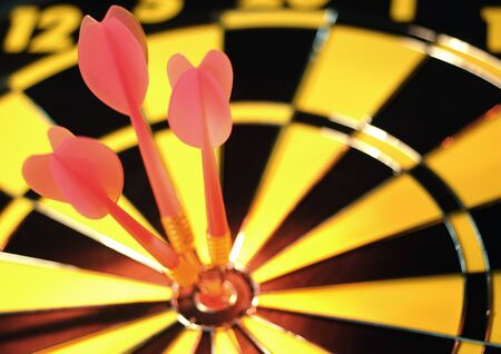 Darts in bulls-eye of dartboard, close-up