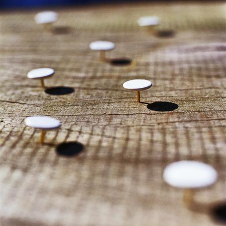 Thumbtacks stuck into wooden surface
