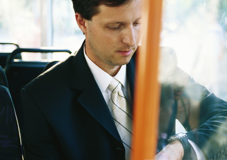 Businessman sitting on bus, checking watch LANG_EVOIMAGES