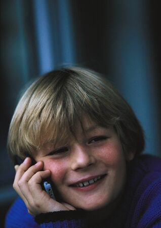 Young boy on phone, smiling, close up