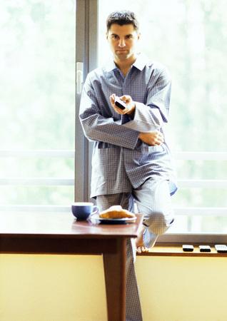 Man in pajamas using remote control
