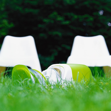 CD case, open on grass, white plastic chairs in background
