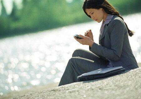 Businesswoman using hand held computer, outdoors