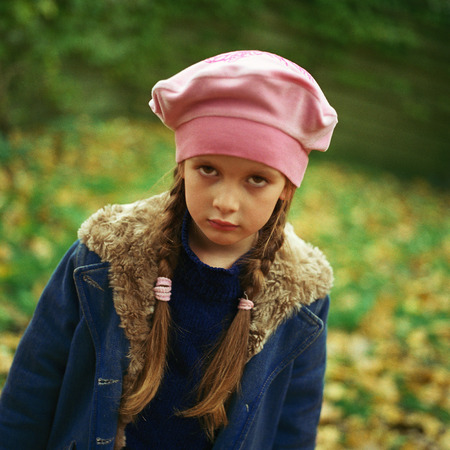 Girl outside wearing pink beret, winter coat, pouting, looking at camera LANG_EVOIMAGES