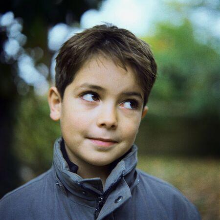Boy wearing coat outside, looking away, portrait