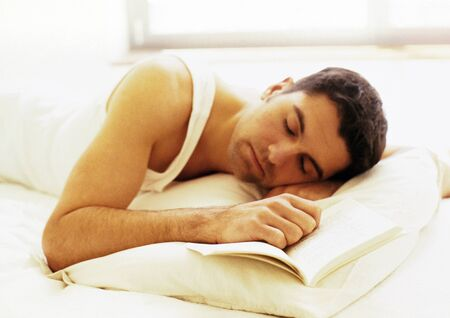 repose: Man lying in bed with hand on book and eyes closed