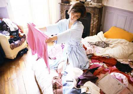 Woman kneeling on bed among piles of clothes, holding up and looking at sweater LANG_EVOIMAGES